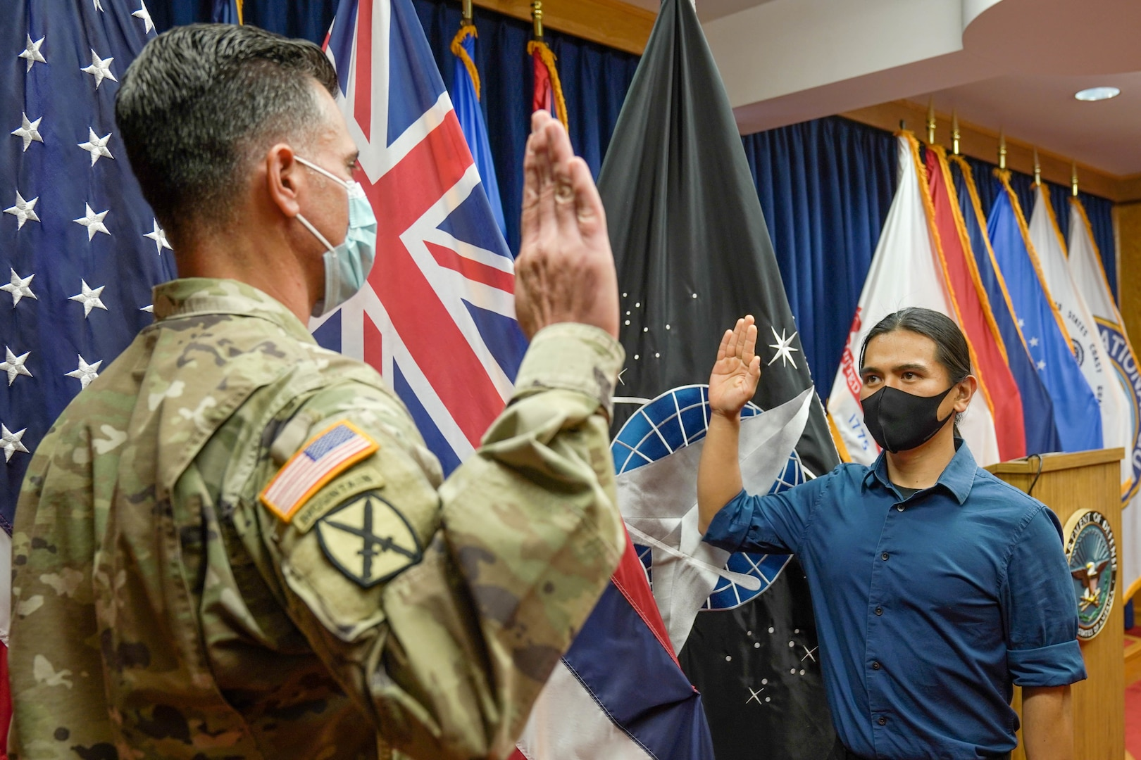 Reyjie Cliff Blando Madriaga, a Hawaiian native, receives the oath of enlistment from U.S. Army Capt. Donald McCoullough, Honolulu Military Entrance Processing Station Officer, as the first Hawaiian U.S. Space Force recruit at Joint Base Pearl Harbor-Hickam, Hawaii, March 4, 2021.