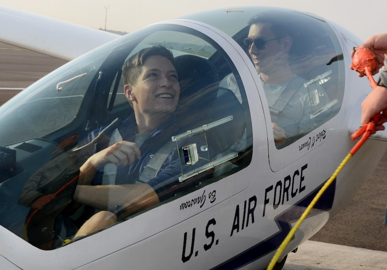 Second Lt. Spencer Brown, a 2021 graduate of the U.S. Air Force Academy and Capt. Brandon Leet, assigned to the 306th Flying Training Squadron, watch as their glider is hook to a tow plane.