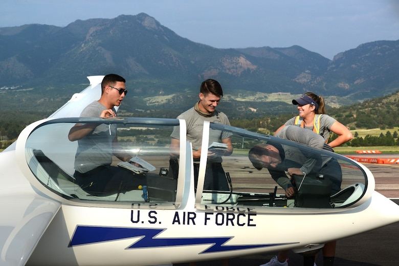 Capt. Brandon Leet, assigned to the 306th Flying Training Squadron, SecondLieutenants Eric Clingenpeel, DJ Alexander and Elizabeth Shaffer, 2021 graduates of the Air Force Academy, complete safety checks on a glider.