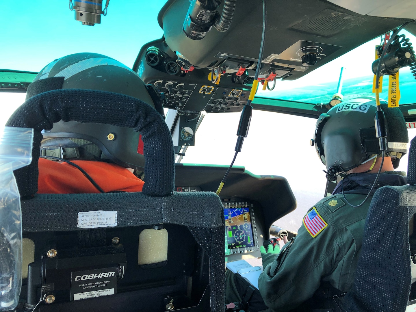 CDR Ryan Popiel flies Rear Adm. Nathan Mooreon the upgraded MH-65E helicopter.