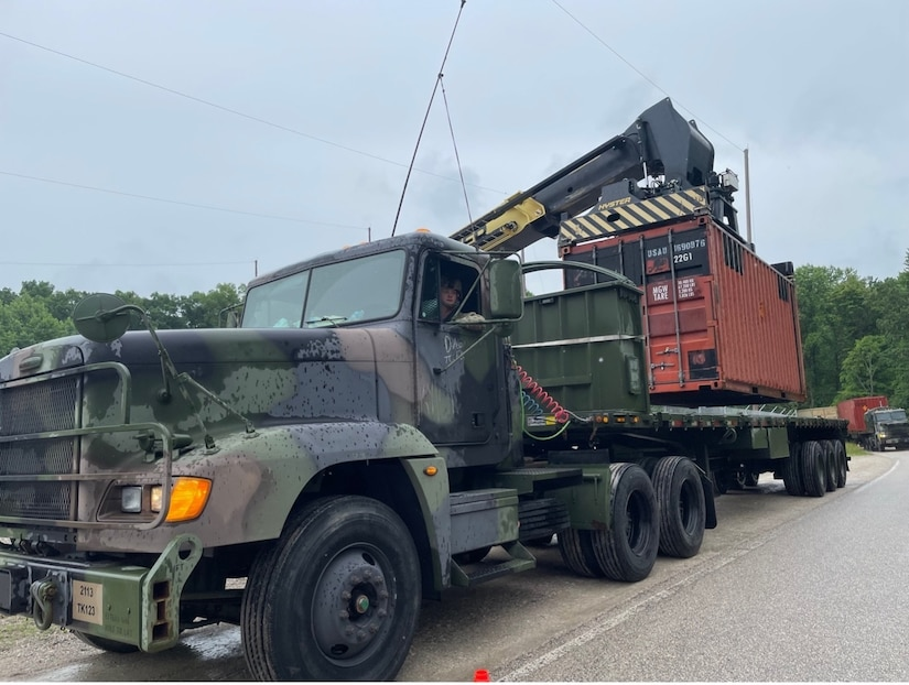 Moving equipment places a cargo container on a truck.