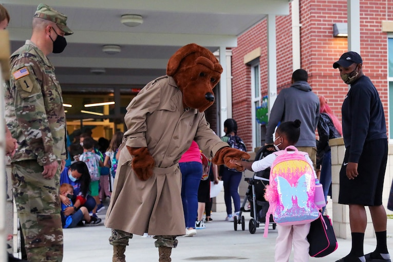 McGruff the Crime Dog greets a little girl as she enters a school.