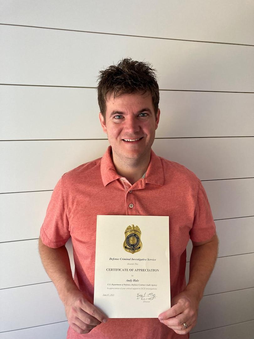 man in orange shirt holding certificate