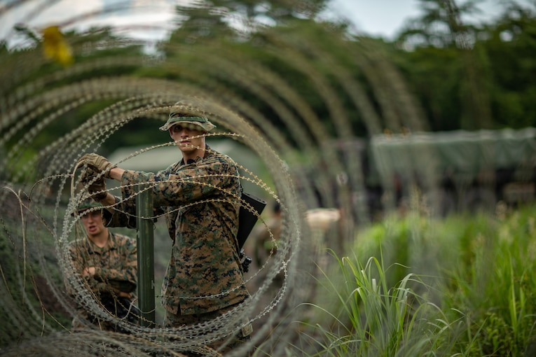 A Marine handles barbed wire forming a barricade outdoors.