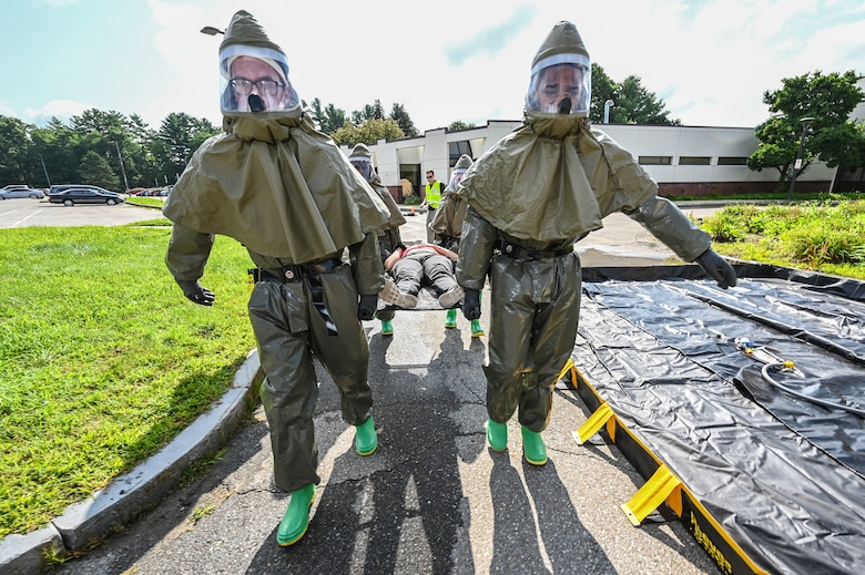 66th Medical Squadron In-Place Patient Decontamination Team members Senior Airmen Gavin Fluery and Ezekiel Grogan, carry an injured role player, Staff Sgt. Leilanie Kenley, 66th Security Forces Squadron NCO in charge of commander support staff, to a decontamination tent during a Ready Eagle exercise at Hanscom Air Force Base, Mass., July 30. The disaster response exercise prepared MDS staff to respond to chemical, biological, radiological, nuclear, or explosive incidents. (U.S. Air Force photo by Todd Maki)