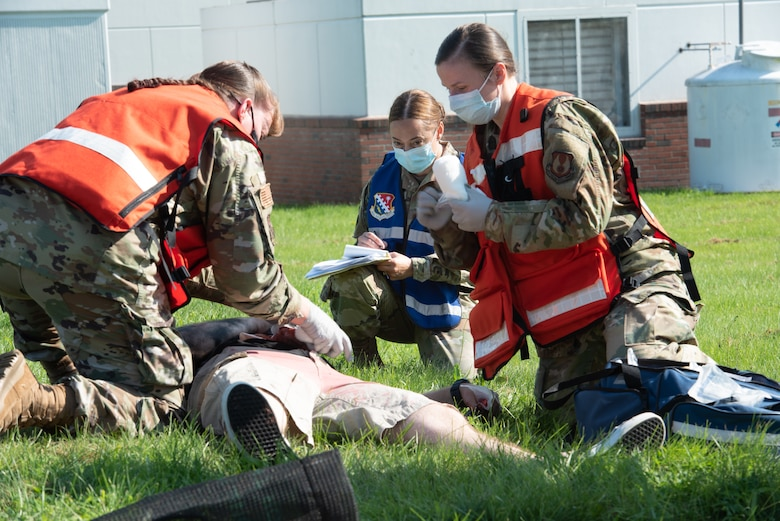 Maj. Andrea Tidd, left, 66th Medical Squadron Field Response Team chief, and Tech Sgt. Tatiana Lieback, 66 MDS Field Response Team member, provide support to a simulated victim during a Ready Eagle exercise at Hanscom Air Force Base, Mass., July 30, while Maj. Stela Strilagas, Inspection Team member, looks on. The full-scale disaster response exercise tested Hanscom medics on their response to a chemical, biological, radiological, nuclear, or explosive event. (U.S. Air Force photo by Todd Maki)