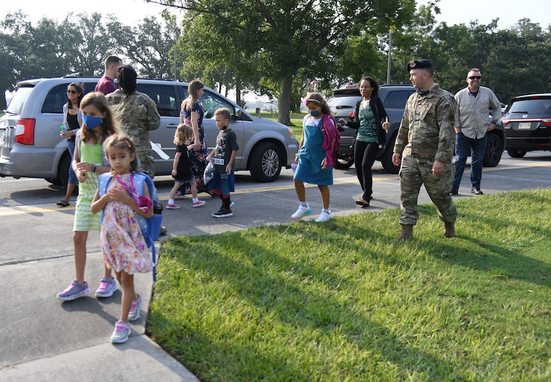 Members of the 81st Security Forces Squadron greet military families for the first day of school near the pedestrian gate at Keesler Air Force Base, Mississippi, Aug. 4, 2021. Defenders and their mascot welcomed the children with stickers as they went to Jeff Davis Elementary School. (U.S. Air Force photo by Kemberly Groue)