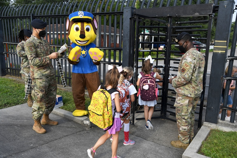 Members of the 81st Security Forces Squadron and Chase the Paw Patrol dog greet military children for the first day of school near the pedestrian gate at Keesler Air Force Base, Mississippi, Aug. 4, 2021. Defenders welcomed the children with stickers as they went to Jeff Davis Elementary School. (U.S. Air Force photo by Kemberly Groue)