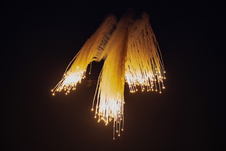 Flares descend in a night sky as an aircraft flies in the background.
