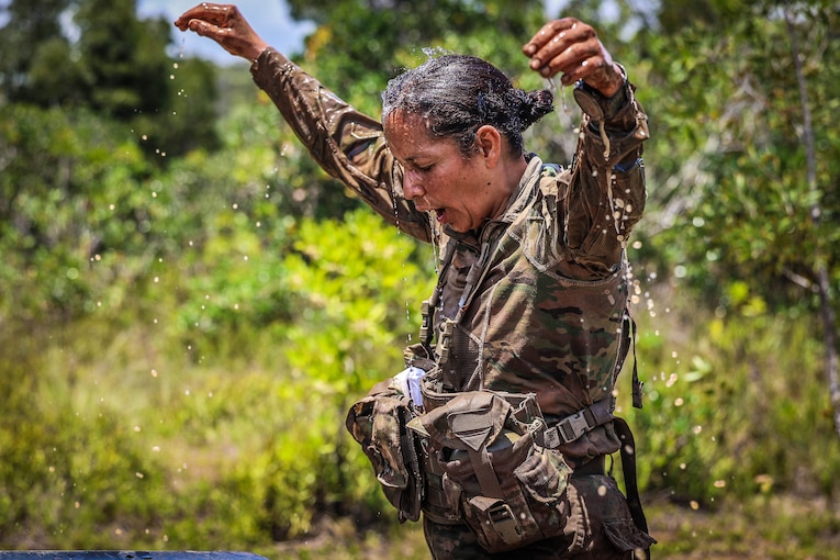A soldier holds arms up as water drips from her saturated uniform.
