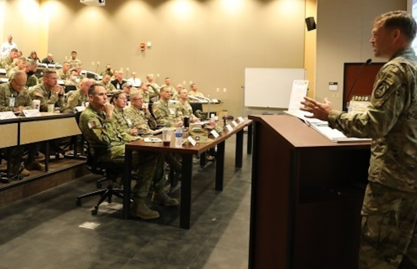 Lt. Gen. Jody J. Daniels, chief of Army Reserve and commanding general, U.S. Army Reserve Command (front table, second from left), participates in the Joint Warfighting Assessment 2021 distinguished visitor day initial briefing at Fort Carson, Colo., June 25, 2021. U.S. Army Civil Affairs and Psychological Operations Command (Airborne) Civil Affairs, Psychological Operations, and Information Operations Soldiers took part in JWA 2021 with participants from different Army units and multinational partners such as U.K., Australian and Canadian armed forces, working to improve interoperability between U.S. joint forces and our allies. JWA exercises help the Army evaluate emerging concepts, integrate new technologies, and promote interoperability between the Army, other services, and our multinational partners. Joint and multinational partners are key to the success of Multi-Domain Operations.