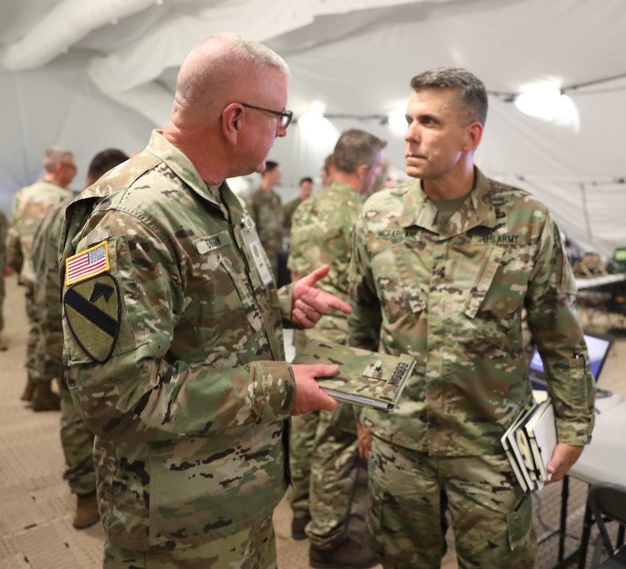 Brig. Gen. Gen. Jeffrey C. Coggin (left), commanding general of the U.S. Army Civil Affairs and Psychological Operations Command (Airborne), speaks with Maj. Gen. Matthew McFarlane, Commanding General, 4th Infantry Division, as they participate in the Joint Warfighting Assessment 2021 distinguished visitor day initial briefing at Fort Carson, Colo., June 25, 2021. U.S. Army Civil Affairs and Psychological Operations Command (Airborne) Civil Affairs, Psychological Operations, and Information Operations Soldiers took part in JWA 2021 with participants from different Army units and multinational partners such as U.K., Australian and Canadian armed forces, working to improve interoperability between U.S. joint forces and our allies. JWA exercises help the Army evaluate emerging concepts, integrate new technologies, and promote interoperability between the Army, other services, and our multinational partners. Joint and multinational partners are key to the success of Multi-Domain Operations.