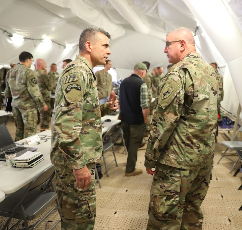 Brig. Gen. Gen. Jeffrey C. Coggin (left), commanding general of the U.S. Army Civil Affairs and Psychological Operations Command (Airborne), speaks with Maj. Gen. Matthew McFarlane, commanding general, 4th Infantry Division, as they participate in the Joint Warfighting Assessment 2021 distinguished visitor day initial briefing at Fort Carson, Colo., June 25, 2021. U.S. Army Civil Affairs and Psychological Operations Command (Airborne) Civil Affairs, Psychological Operations, and Information Operations Soldiers took part in JWA 2021 with participants from different Army units and multinational partners such as U.K., Australian and Canadian armed forces, working to improve interoperability between U.S. joint forces and our allies. JWA exercises help the Army evaluate emerging concepts, integrate new technologies, and promote interoperability between the Army, other services and, our multinational partners. Joint and multinational partners are key to the success of Multi-Domain Operations.