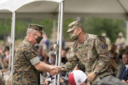 (right) U.S. Army Central outgoing Commanding General, Lt. Gen. Terry Ferrell, shakes the U.S. Central Command's Commander, Marine Corps Gen. Kenneth McKenzie's hand after his remarks during USARCENT's Change of Command ceremony at Patton Hall's Lucky Park on Shaw Air Force Base, S.C., Aug. 4, 2021. Mckenzie officiated the ceremony for CENTCOM's Army Service Component Command. (U.S. Army photo by Sgt. Leo Jenkins)
