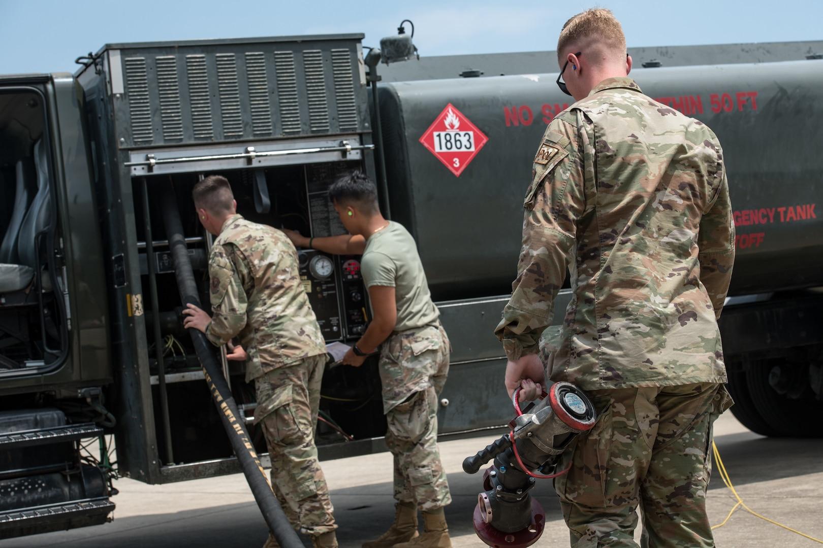 Men move a fuel hose back onto a truck