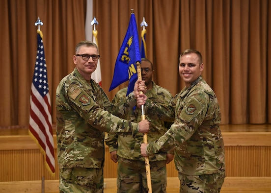 Two military members hold a flag as a part of a ceremony.