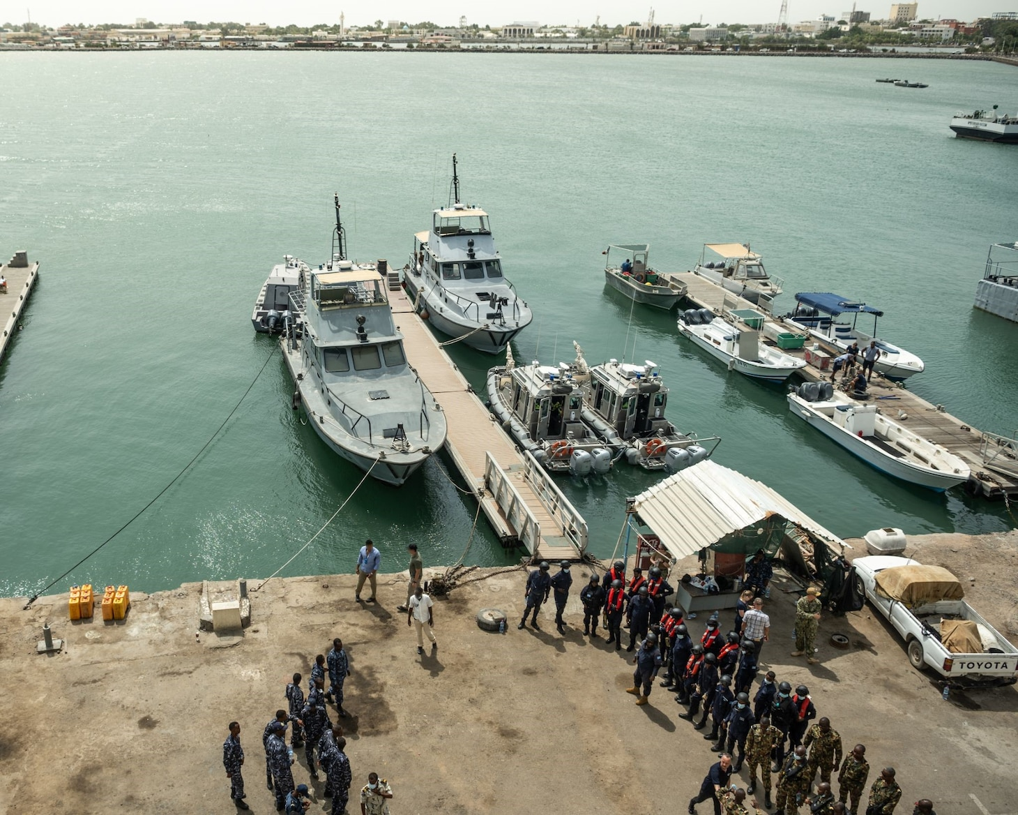 (Aug. 2, 2021) Djiboutian, Somalian, Comorian and U.S. service members review visit, board, search and seizure (VBSS) procedures before practicing simulated scenarios during exercise Cutlass Express 2021 at L'Escale Marina, Djibouti, Aug. 2, 2021. VBSS is conducted to capture and control a suspected enemy vessel to combat terrorism, piracy and smuggling operations at sea. Exercise Cutlass Express, sponsored by U.S. Africa Command and facilitated by U.S. Naval Forces Europe and Africa/U.S. Sixth Fleet, is designed to improve regional cooperation, maritime domain awareness and information sharing practices to increase capabilities between the U.S., East African and Western Indian Ocean nations to counter illicit maritime activity.