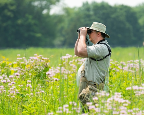 Ed Wolski looks for hummingbirds and other wildlife July 19 on Huffman Prairie at Wright-Patterson Air Force Base. Wolski works as a civilian at the National Air and Space Intelligence Center.