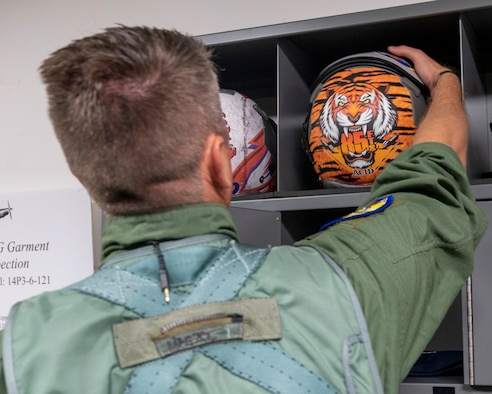 """U.S. Air Force Lt. Col. Brian """"Tiger King"""" Tripp, 85th Flying Training Squadron commander, grabs his flight helmet on Tiger Day before his flight at Laughlin Air Force Base, Texas on August 5, 2021. Pilots on Tiger Day took to the sky to celebrate their heritage for being a part of the 85th Flying Training Squadron in a competition against fellow instructor pilots. (U.S. Air Force Photo by Senior Airman Nicholas Larsen)"""