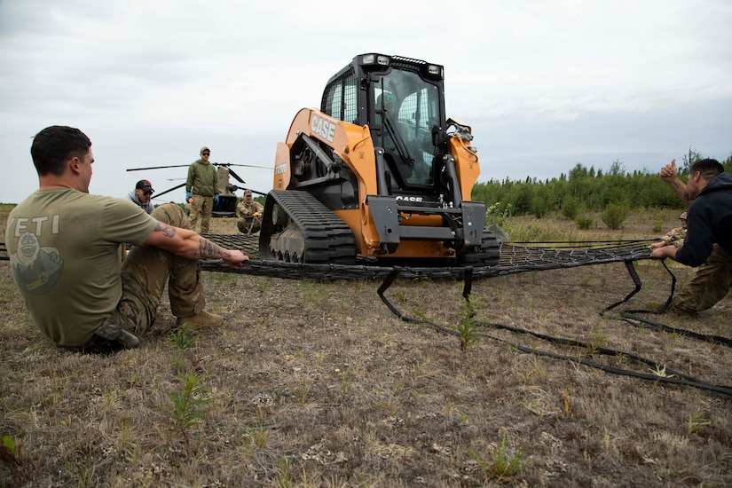 A 211th General Support Aviation Battalion CH-47 Chinook helicopter transports a skid-steer loader by slingload from Nicolai to the community of Telida, Alaska, as part of the Innovative Readiness Training program on July 27, 2021. The IRT program is designed to enhance mission readiness while addressing the needs within America's communities. (U.S. Army National Guard photo by Victoria Granado)