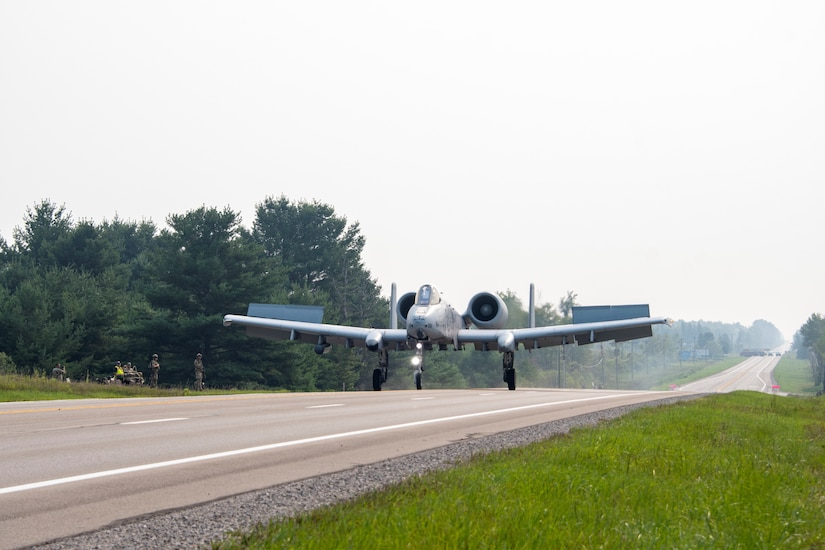 A photo of an A-10 landing on a highway