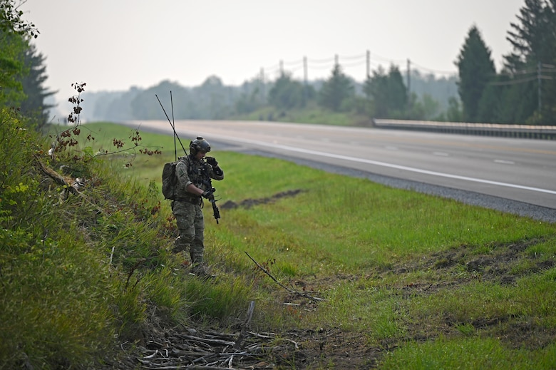 A Special Tactics operator from the 24th Special Operations Wing surveys and prepares a closed section of U.S. Highway 32 in order to land and receive several A-10 Thunderbolt IIs assigned to the 127th and 355th Wings as well as C-146A Wolfhounds assigned to the 492nd and 919th Special Operations Wings during exercise Northern Strike 21 Aug. 5, 2021, in Alpena, Mich. Special Tactics Airmen are the Air Force's special operations ground force, experienced in conducting global access missions such as establishing austere landing zones around the world.  (U.S. Air Force photo by Staff. Sgt Ridge Shan)