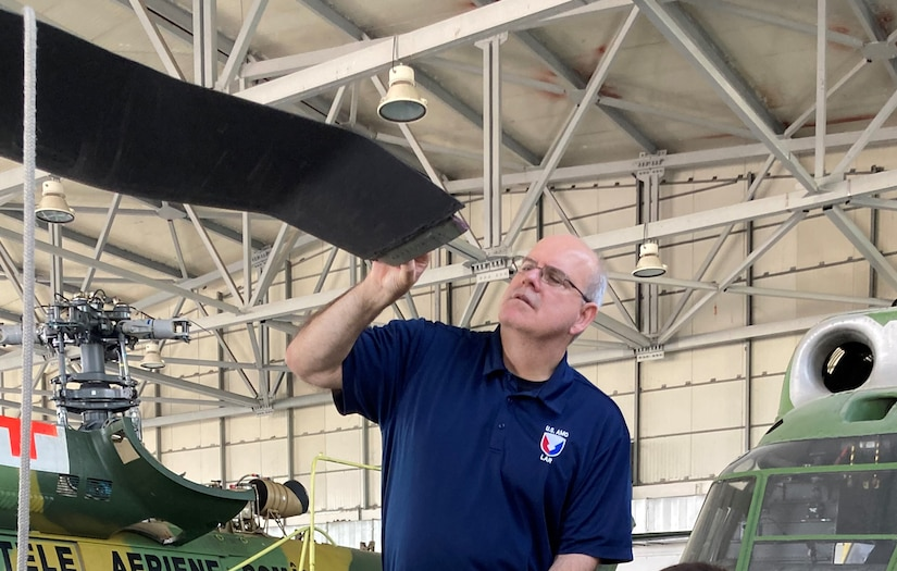 Cliff Barnes, a U.S. Army Aviation and Missile Command Logistics Assistance Representative assigned to the 405th Army Field Support Brigade, inspects a damaged rotor blade on a UH-60 Black Hawk in a hangar at Bucharest International Airport. After the precautionary landing due to a major mechanical problem, Barnes inspected the aircraft with the pilots and mechanics. They looked at all the parts, and Barnes pinpointed what needed to be replaced. (U.S. Army courtesy photo)