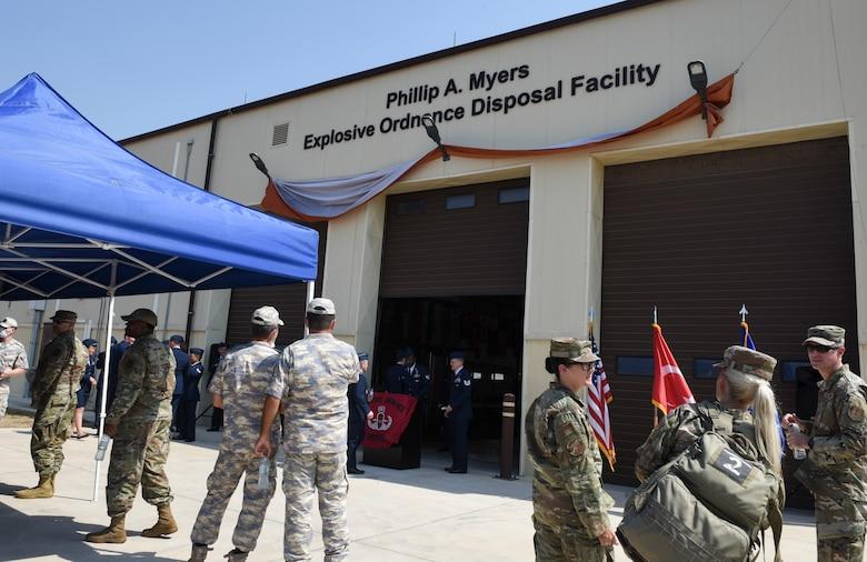 Airmen stand near EOD facility.