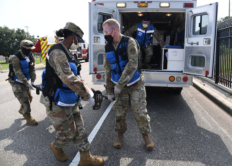 """Members of the 81st Medical Group prepare to load a """"victim"""" in the back of an ambulance during a Chemical, Biological, Radiological, Nuclear exercise at Keesler Air Force Base, Mississippi, Aug. 6, 2021. The Ready Eagle exercise tested the base's ability to respond to and recover from a mass casualty event. (U.S. Air Force photo by Kemberly Groue)"""