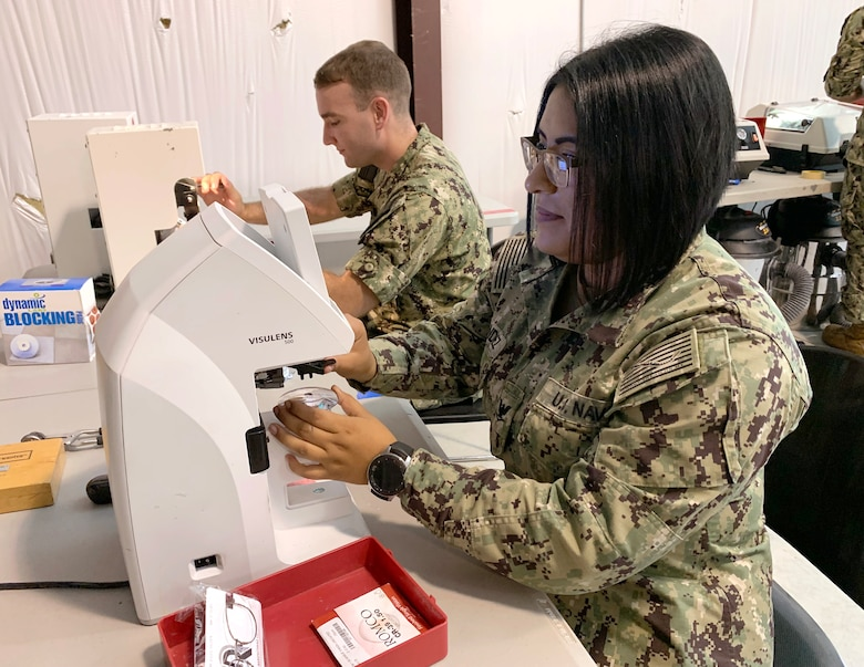 U.S. Navy Petty Officer 3rd Class Leticia Hernandez (right) and Petty Officer 2nd Class Joseph Kraus, assigned to the Naval Ophthalmic Support and Training Activity, Yorktown, Virginia, operate lensmeters to help fabricate eyeglasses for Operation Healthy Delta at the medical site in Sikeston, Missouri, June 16. The operation is a U.S. Department of Defense Innovative Readiness Training mission, offering readiness training to multi-service, interagency, and community partners, while providing no-cost healthcare to the community. (U.S. Air National Guard Photo by Major Mary Hook/Released)