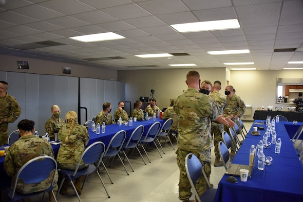 A photo of Airmen standing in a room.