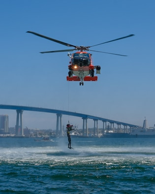 A U.S. Coast Guard MH-60J helicopter piloted by U.S. Coast Guard Lt. j.g. Tara Strauss hoists an Airmen out of the ocean while rescue swimmer Chief Petty Officer Tyler Holt prepares to drop back into the water at Naval Amphibious Air Base Coronado in San Diego, July 9. Pilots must complete water survival training every three years to maintain combat readiness.  (U.S. Air National Guard photo by Staff Sgt. Aubrey Pomares)