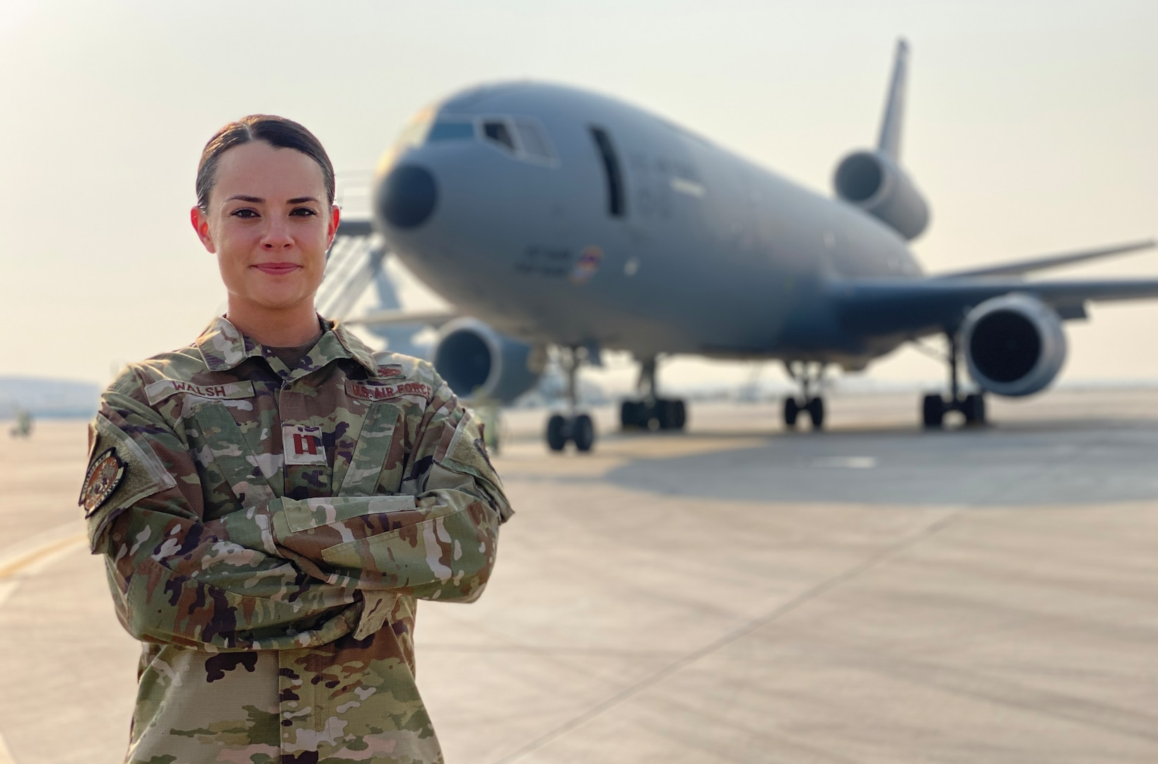 Female service member poses in front of aircraft