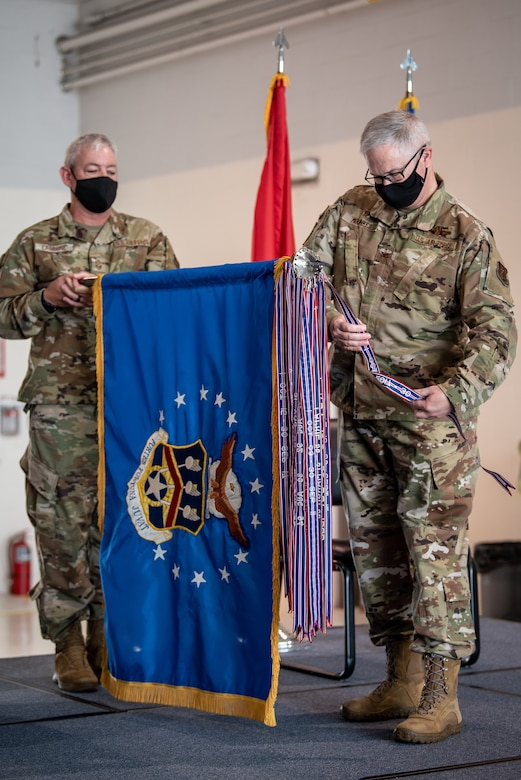 Col. David Mounkes (right), outgoing commander of the 123rd Airlift Wing, pins a streamer representing the wing's 19th Air Force Outstanding Unit Award to the wing guidon during a ceremony at the Kentucky Air National Guard Base in Louisville, Ky., Aug. 7, 2021. The award, which is bestowed on the top 10 percent of all units, recognizes the wing's outstanding achievement across a full spectrum of operations, from homeland disaster response to the war effort overseas, between October 2017 and September 2019. No other airlift unit in the United States Air Force — active duty, Guard or Reserve — has earned 19 AFOUAs. (U.S. Air National Guard photo by Dale Greer)