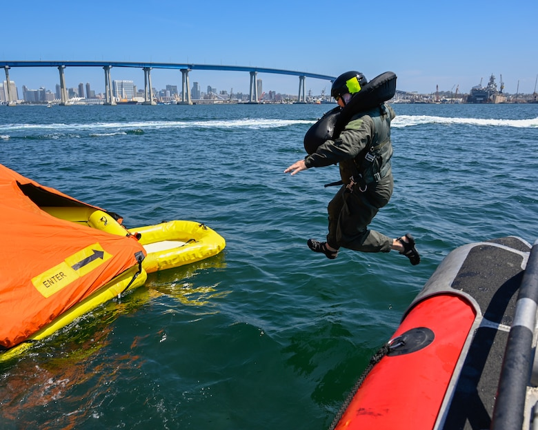 U.S. Air Force Tech Sgt. Alexandria Panduro, aircrew flight equipment technician at the 144th Fighter Wing, jumps towards the life raft to prepare for the helicopter extraction at Naval Amphibious Air Base Coronado, San Diego, July 10. Pilots must complete water survival training every three years to maintain combat readiness. (U.S. Air National Guard photo by Staff Sgt. Aubrey Pomares)
