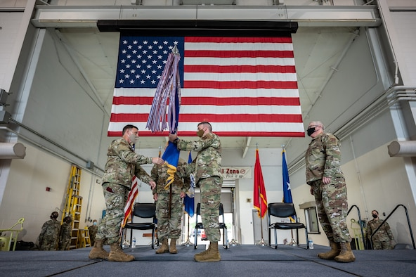 Col. Bruce Bancroft (center) accepts the 123rd Airlift Wing guidon from Brig. Gen. Jeffrey Wilkinson (left), Kentucky's assistant adjutant general for Air, during a ceremony at the Kentucky Air National Guard Base in Louisville, Ky., Aug. 7, 2021, formally recognizing Bancroft's assumption of command of the wing from Col. David Mounkes (right). Mounkes, who had served as wing commander since 2016, has been named director of policy for air operations, plans and programs at Joint Forces Headquarters—Kentucky. (U.S. Air National Guard photo by Dale Greer)