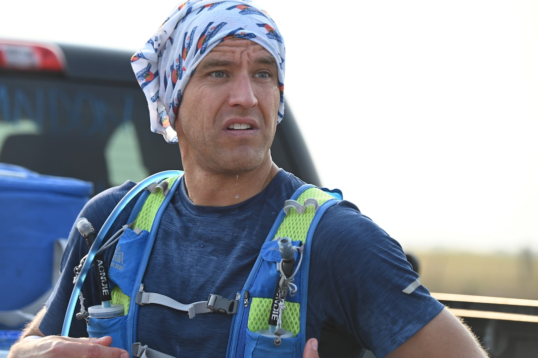 A portrait of Senior Master Sgt. Brandon Miller with sweat dripping off his chin at a checkpoint rest during the Maah Daah Hey Trail 107.3-mile ultramarathon held in the western North Dakota badlands July 31 through Aug. 1, 2021.