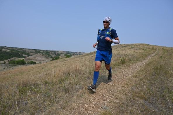 Senior Master Sgt. Brandon Miller runs down a dirt path in the rugged badlands of North Dakota during the Maah Daah Hey Trail 107.3-mile ultramarathon held July 31 through Aug. 1, 2021.