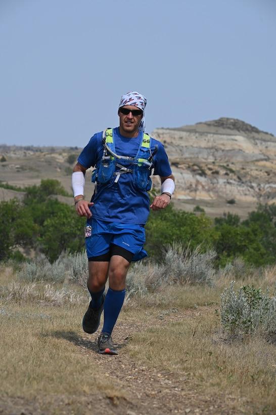 Senior Master Sgt. Brandon Miller runs on the rugged, dirt path of the Maah Daah Hey Trail in the badlands of western North Dakota during a 1007.3-mile ultramarathon running race July 31, 2021.