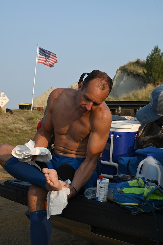Senior Master Sgt. Brandon Miller looks at his bare foot as he rests at a checkpoint location on the Maah Daah Hey Trail 107.3-mile ultramarathon running race in the North Dakota badlands July, 31, 2021.