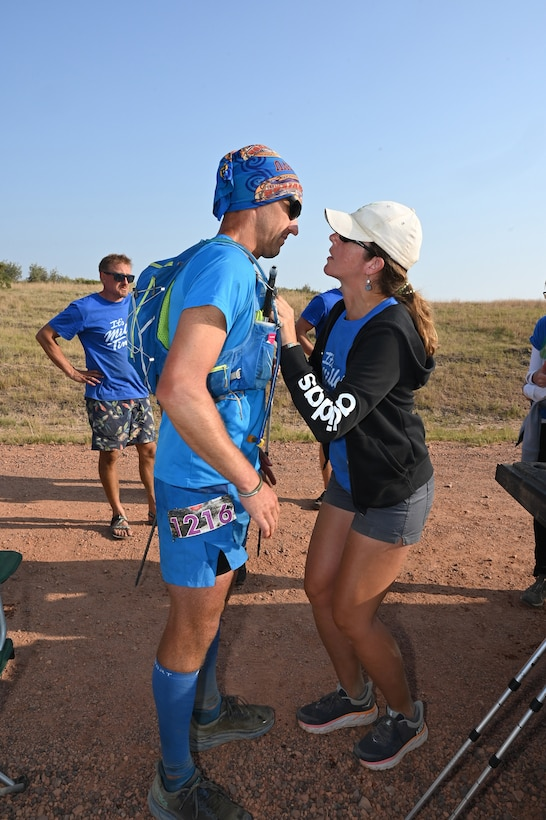 Senior Master Sgt. Brandon Miller listens to his girlfriend of over three years, as she encourages him to finish the last leg of the 107.3-mile Maah Daah Hey Trail ultramarathon running race through the rugged badlands of North Dakota Aug. 1, 2021.