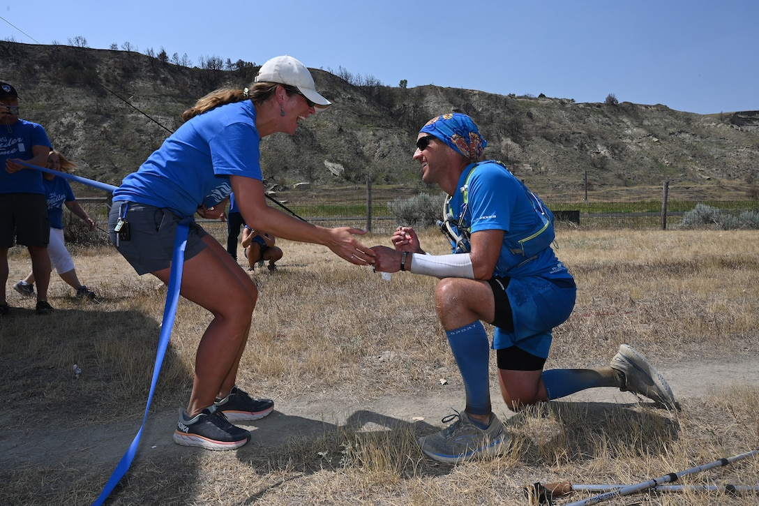 Senior Master Sgt. Brandon Miller is down on one knee as he successfully proposes marriage to his girlfriend of over three year at the finish line of the Maah Daah Hey Trail ultramarathon, Medora, N.D., Aug. 1, 2021.
