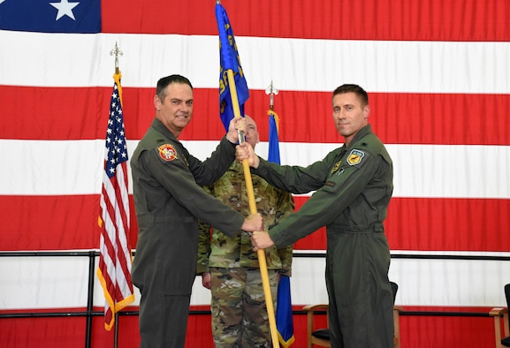 U.S. Air Force Col. Michael Leonas, the 442d Operations Group Commander, left, passes the unit flag to Lt. Col. Ryan Hodges, the incoming 303rd Fighter Squadron Commander, during the 303rd change of command ceremony on Aug. 7, 2021, at Whiteman Air Force Base, Mo. (U.S. Air Force photo by Senior Airman Alex Chase)