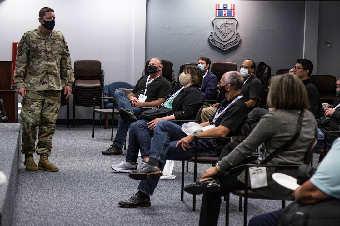 Military commander speaks in front of seated civilian employers.
