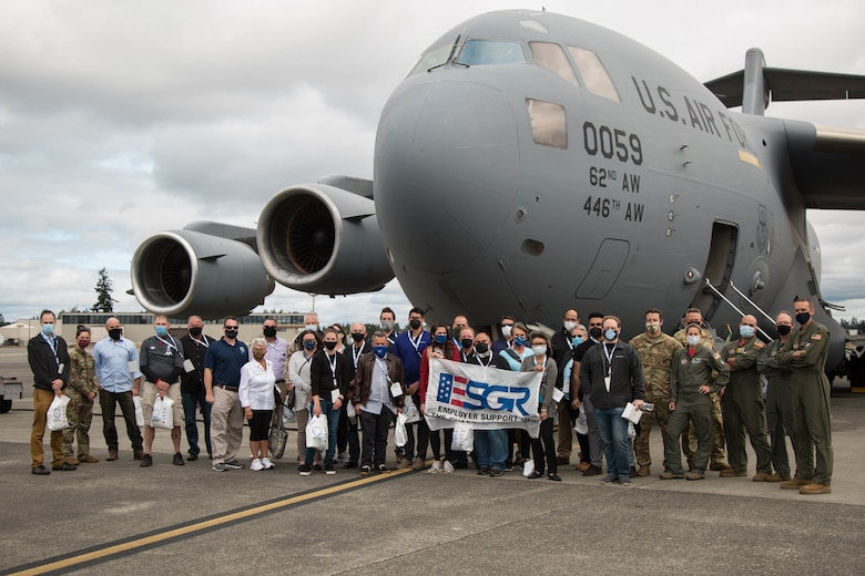 Civilian employers pose for a group photo in front of a C-1 7 Globemaster III