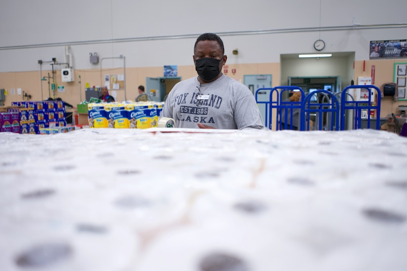JOINT BASE ELMENDORF-RICHARDSON, Alaska -- Charlie Jones, Anchorage Area Commissary store associate, tags inventory before a Commissary sale Aug. 7, 2021, at the Alaska Army National Guard Aviation Facility, Bethel, Alaska. An Alaska Air National Guard C-17 Globemaster III moved tons of groceries and supplies from Joint Base Elmendorf-Richardson to Bethel to offer the goods to eligible residents at discount prices. (U.S. Air National Guard photo by David Bedard/Released)