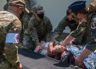 Servicemembers in uniform prepare to lift a simulated patient onto a stretcher.