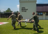 Four servicemembers in uniform, carry a simulated patient on a stretcher.