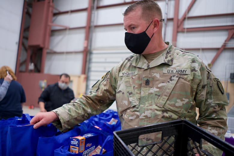JOINT BASE ELMENDORF-RICHARDSON, Alaska -- Command Sgt. Maj. James Nyquist, state command sergeant major for the Alaska Army National Guard, arranges Alaska USO care packages before a Commissary sale Aug. 7, 2021, at the Alaska Army National Guard Aviation Facility, Bethel, Alaska. An Alaska Air National Guard C-17 Globemaster III moved tons of groceries and supplies from Joint Base Elmendorf-Richardson to Bethel to offer the goods to eligible residents at discount prices. (U.S. Air National Guard photo by David Bedard/Released)