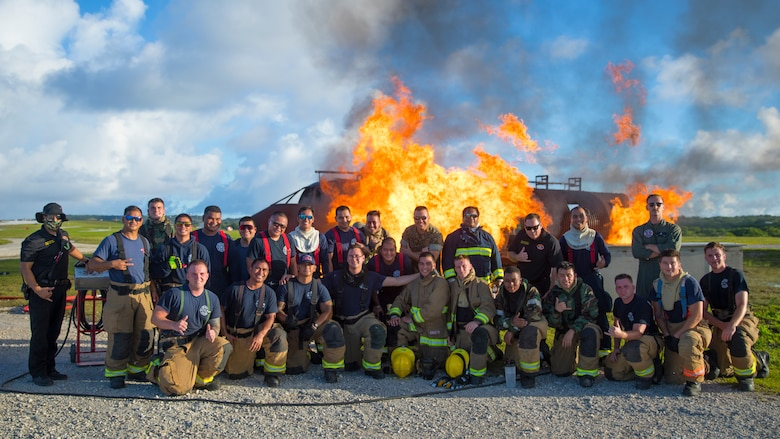 U.S. Marines with Marine Wing Support Squadron 171 and Airmen with the Andersen Air Force Base Fire and Emergency Services, 36th Civil Engineer Squadron and Guam International Airport Fire Department crash fire rescue personnel pose for a photo during a controlled burn exercise at Andersen Air Force Base, Guam, July 28, 2021. Marines, Airmen, and Guam International Airport Fire Department crash fire rescue take part in annual training exercises in order to remain proficient in firefighting and rescue procedures to ensure safe airfield operations. (U.S. Marine Corps photo by Lance Cpl. Tyler Harmon)